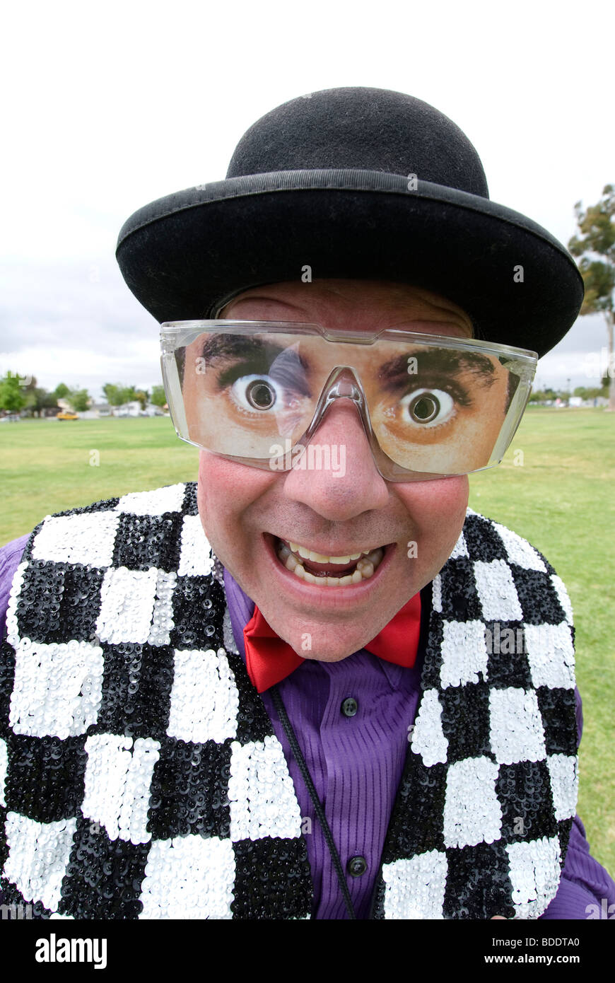 A magician entertainer with fake eyeglasses smiles into the camera. - Stock Image