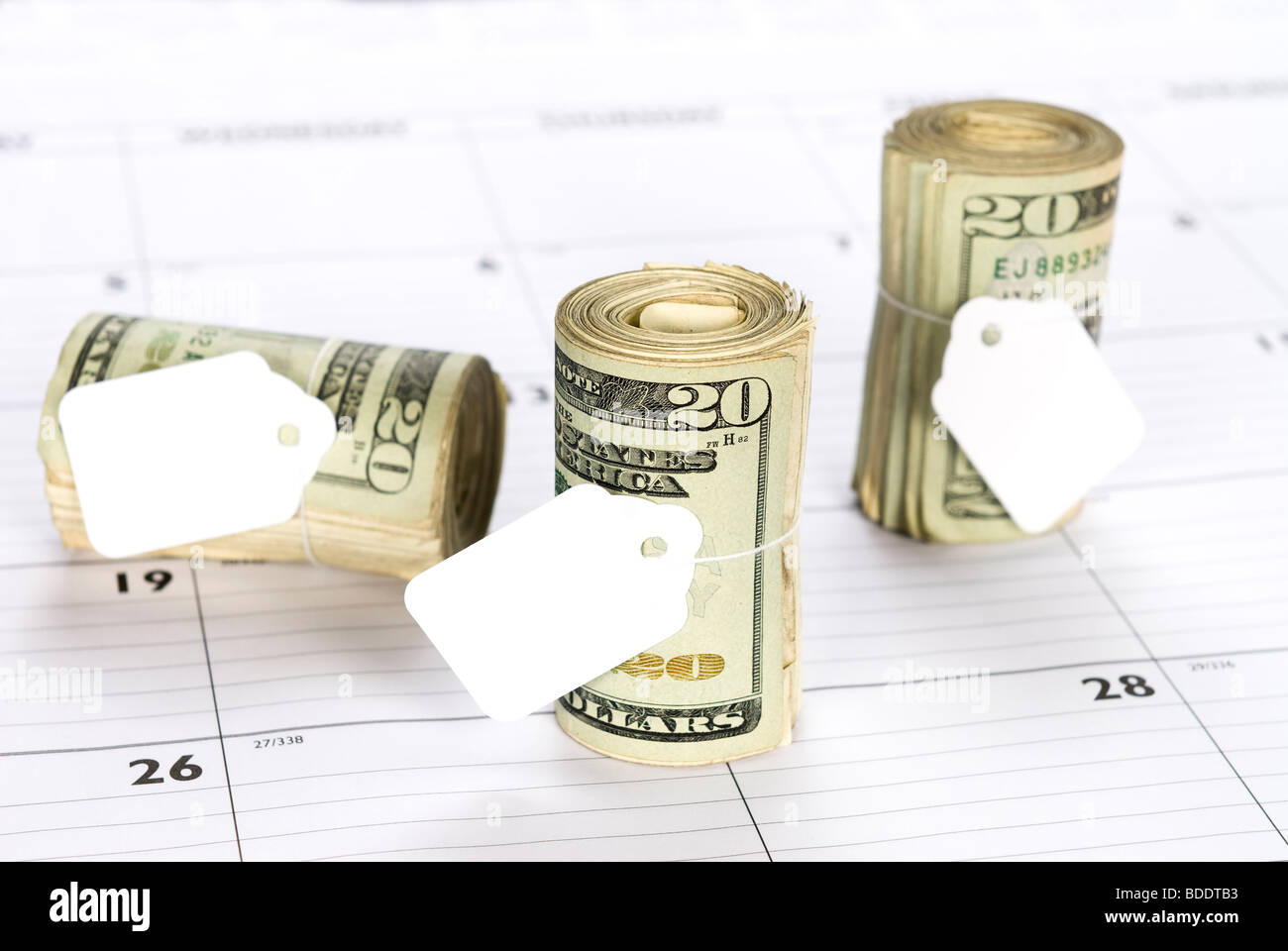 Cash money rolls on a desk calendar with blank tags for copy - Stock Image