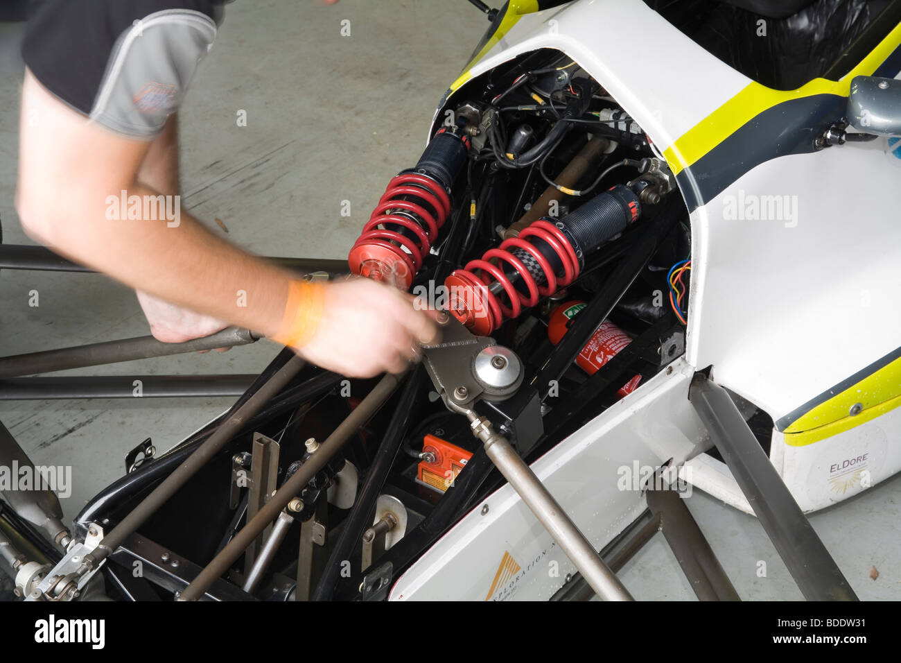 Hands of mechanic working on shock absorber setup on an open