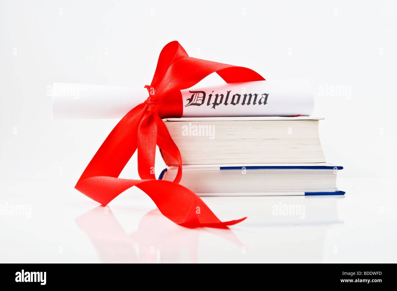 Diploma with red ribbon and books on white background - Stock Image
