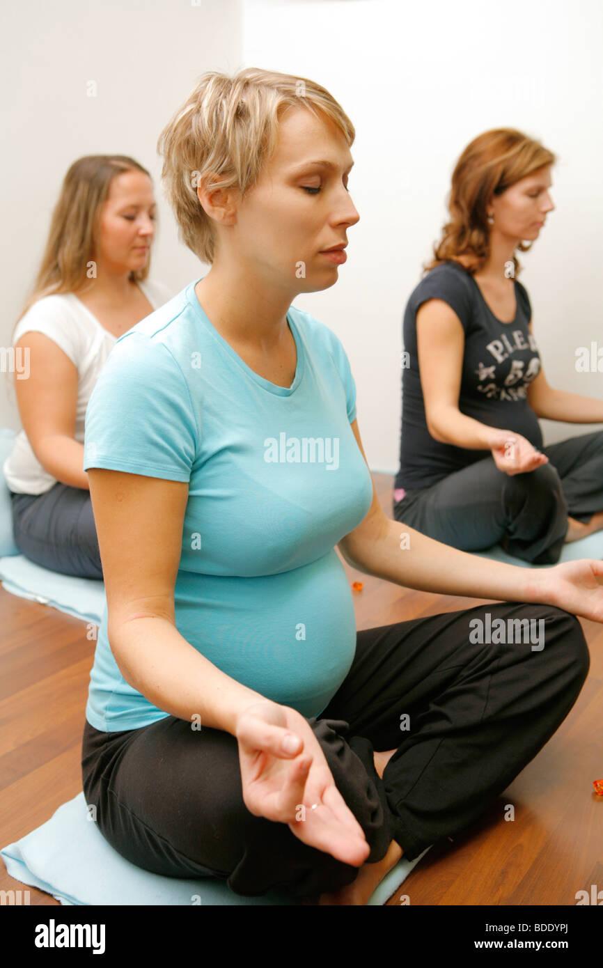 Pregnant women exercising yoga Stock Photo