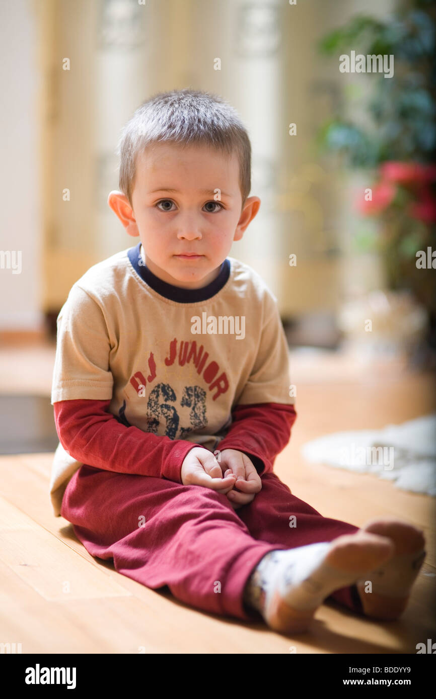 Portrait of a little boy sitting on the floor - Stock Image