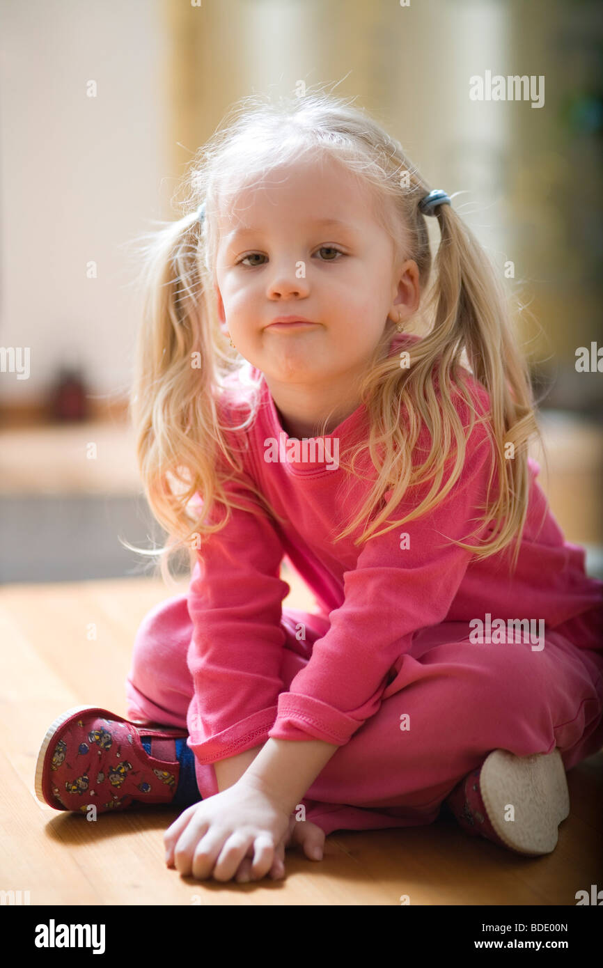 Portrait of a little girl sitting on the floor - Stock Image