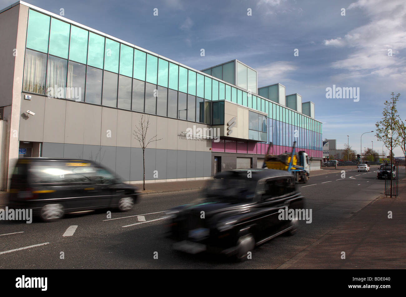 IRELAND, North, Belfast, West, Falls Road, Exterior of the refurbished Falls Swimming Baths with black taxi cabs - Stock Image
