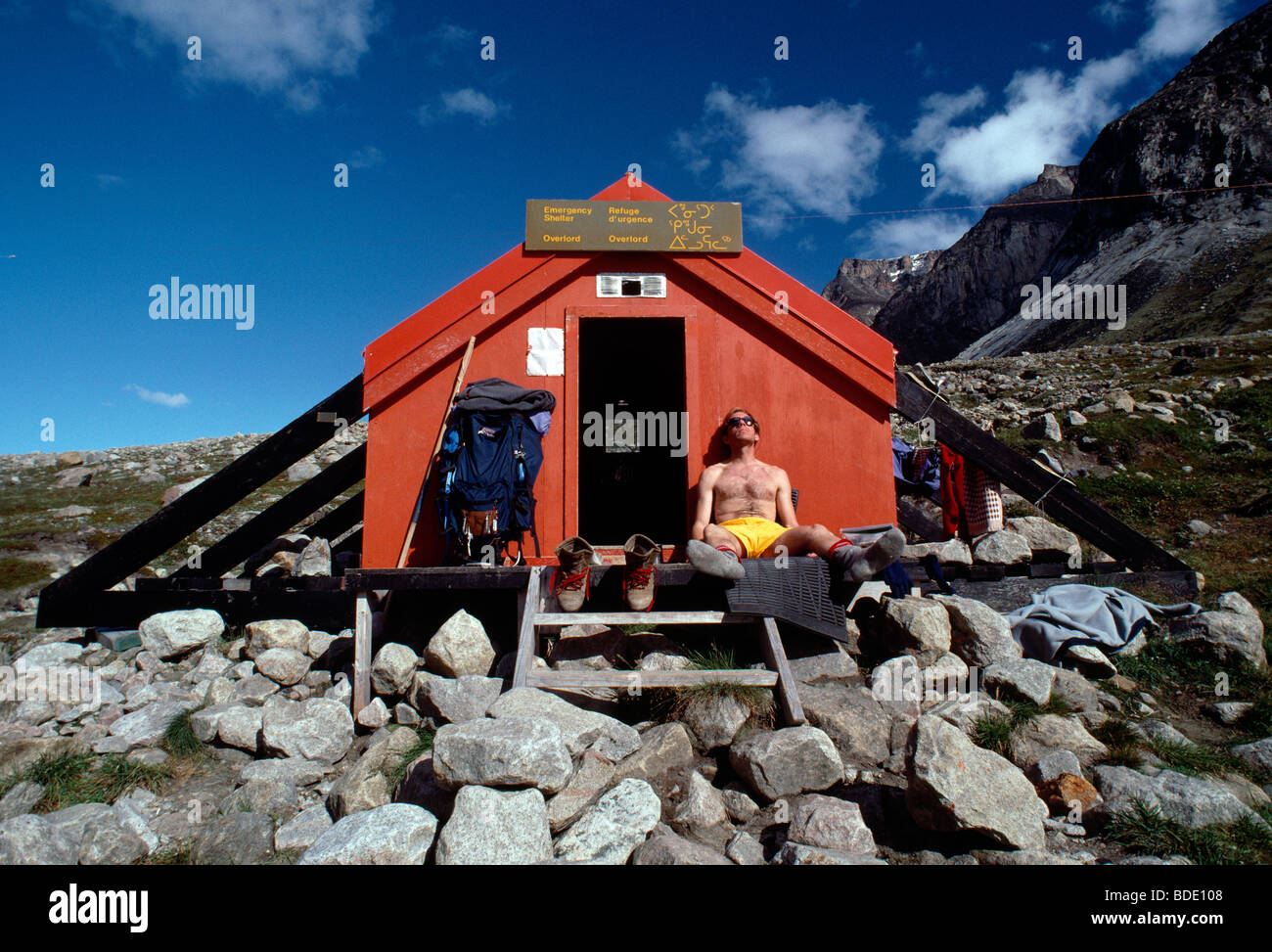 Explorer H. Mark Weidman relaxes in the sun at the Overlord emergency shelter in Auyuittuq National Park, Baffin - Stock Image