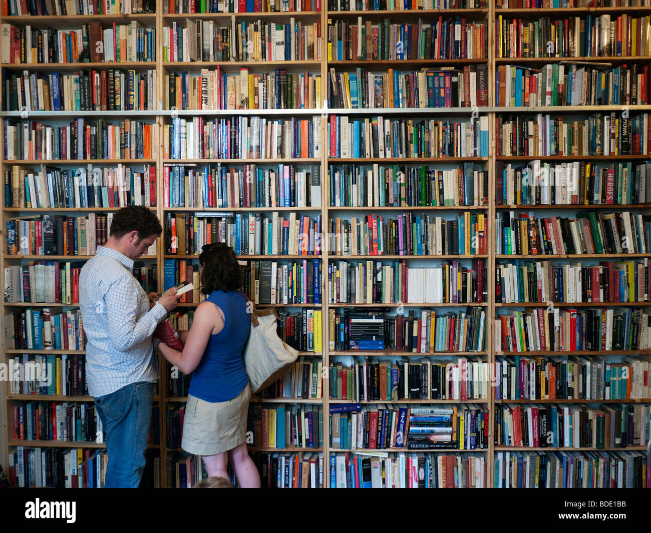 Couple browsing in a bookstore in Prenzlauer Berg in Berlin Germany - Stock Image