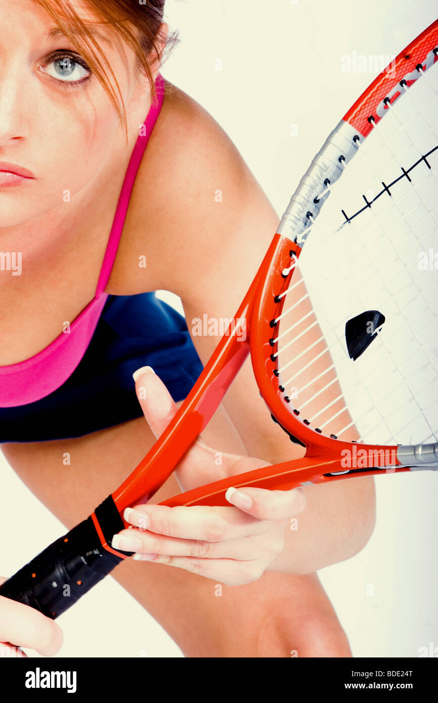 Young woman playing tennis preparing to hit the ball - Stock Image