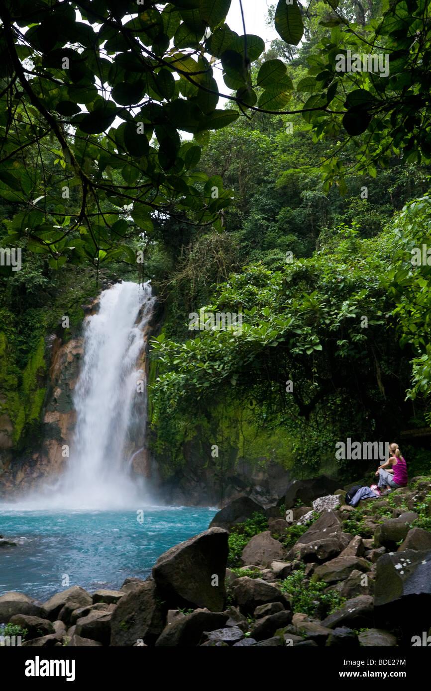 Female hiker resting beneath a waterfall along the vibrant blue Rio Celeste river in Tenorio Volcano National Park, Stock Photo