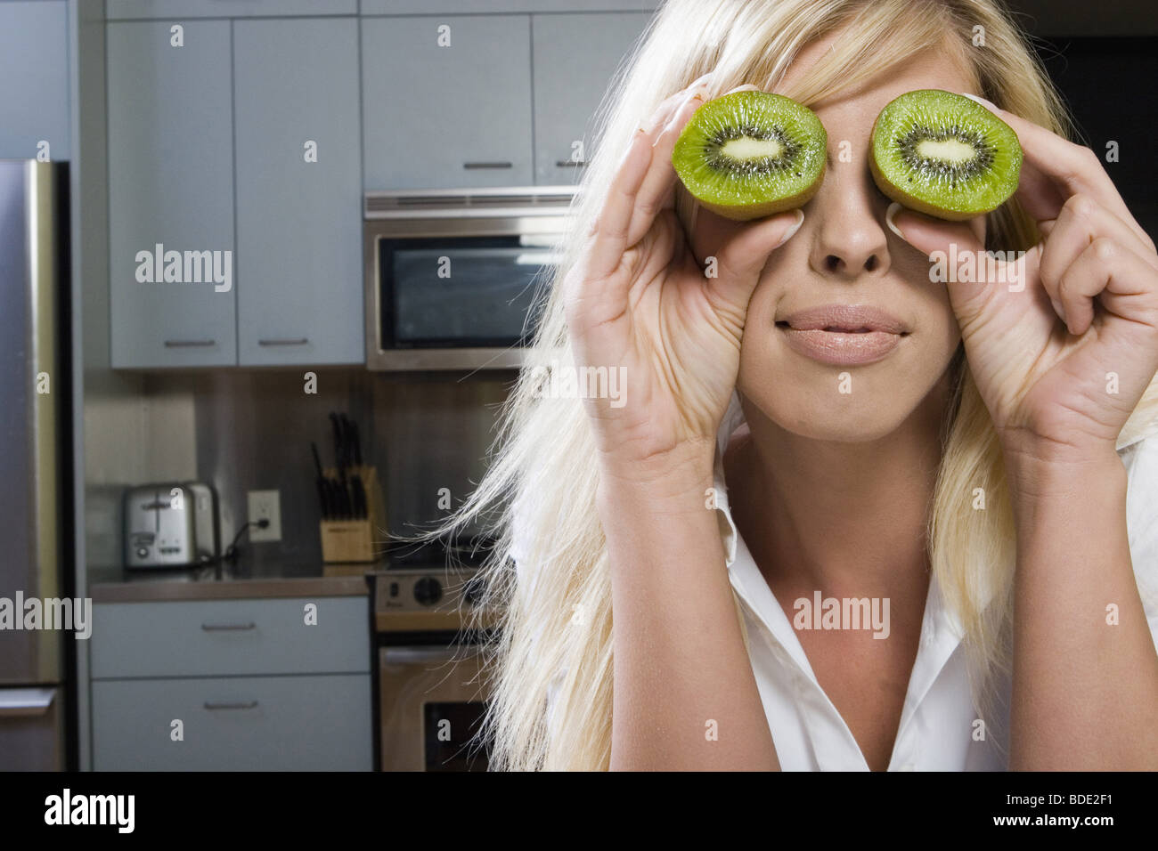 Young woman acting goofy while preparing a meal - Stock Image