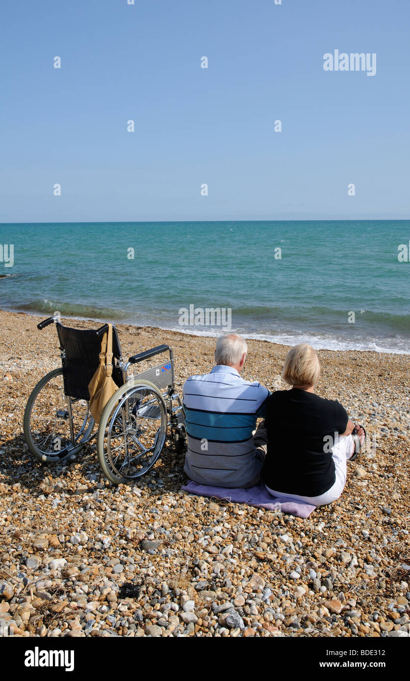 Man and woman on pebble beach with a wheelchair during summer Sunbathing couple at Bognor Regis West Sussex southern - Stock Image