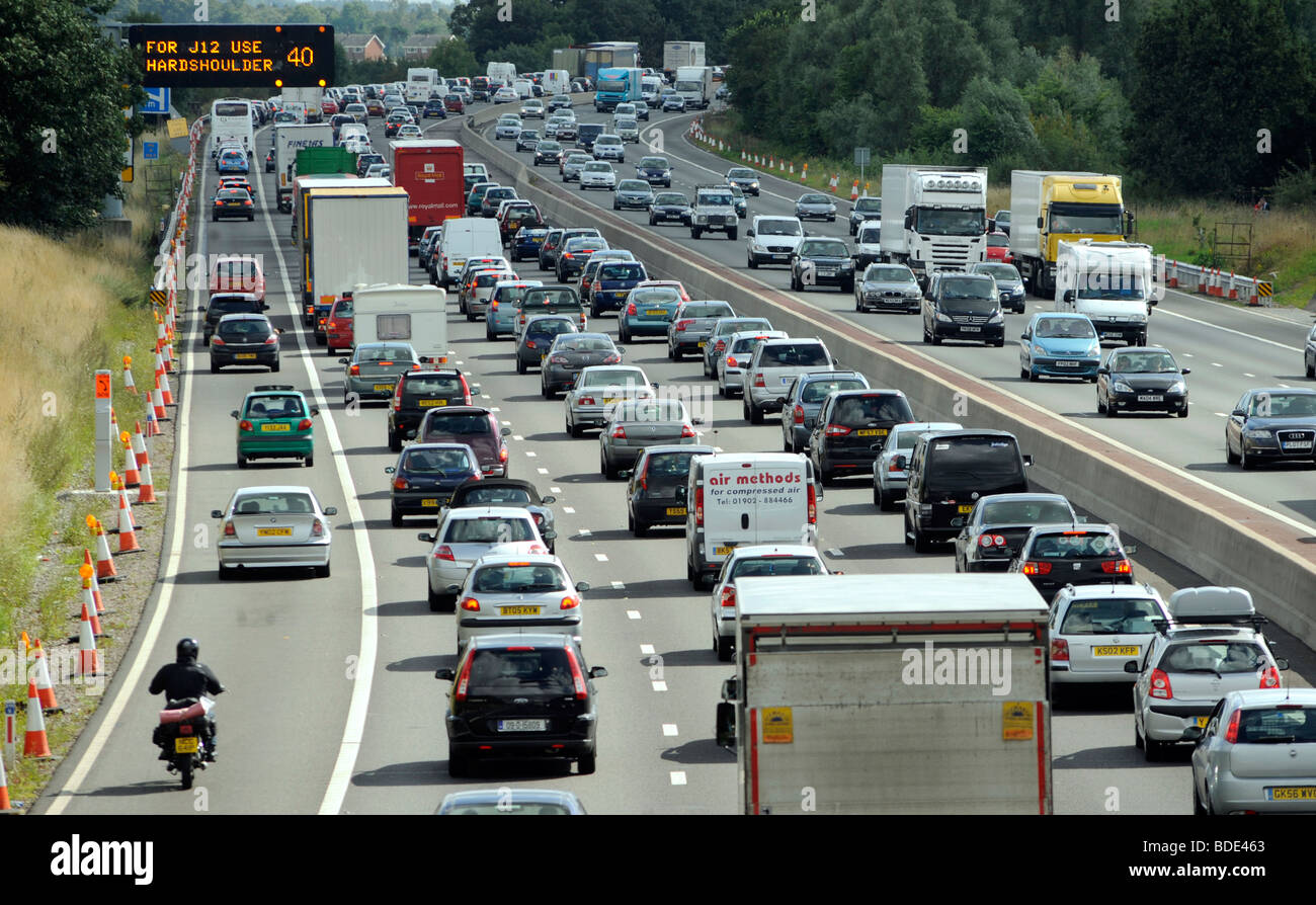 HEAVY TRAFFIC ON THE M6 MOTORWAY NEAR JUNCTION 12 IN STAFFORDSHIRE WITH GANTRY SIGN SAYING USE HARD SHOULDER ,40MPH - Stock Image