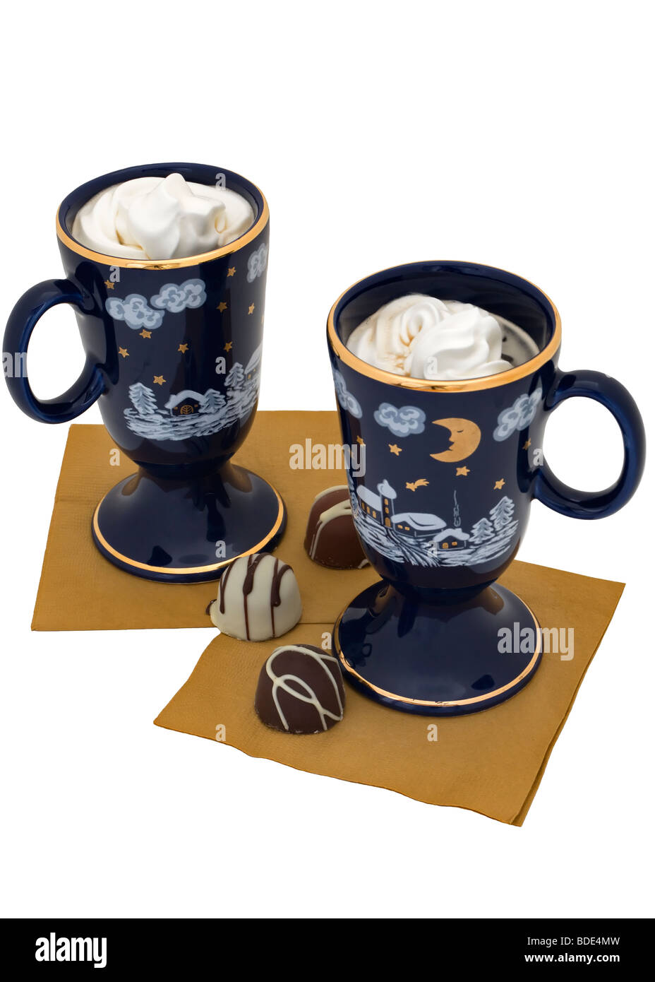 Two coffee dessert drinks are topped with whipped cream and served with chocolate truffles. - Stock Image