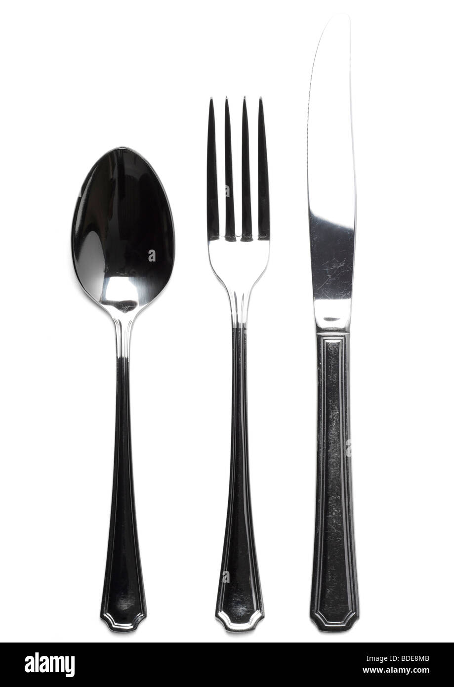 Old knife, fork and dessert spoon on white background - Stock Image