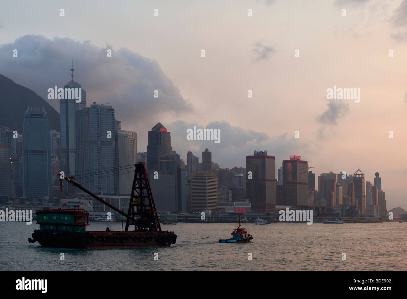 Tug pulling boat in Victoria Harbour in Hong Kong, China. - Stock Image