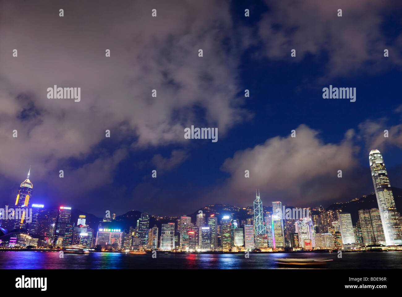 View across Victoria Harbour of high rise buildings at night in Hong Kong, China. - Stock Image