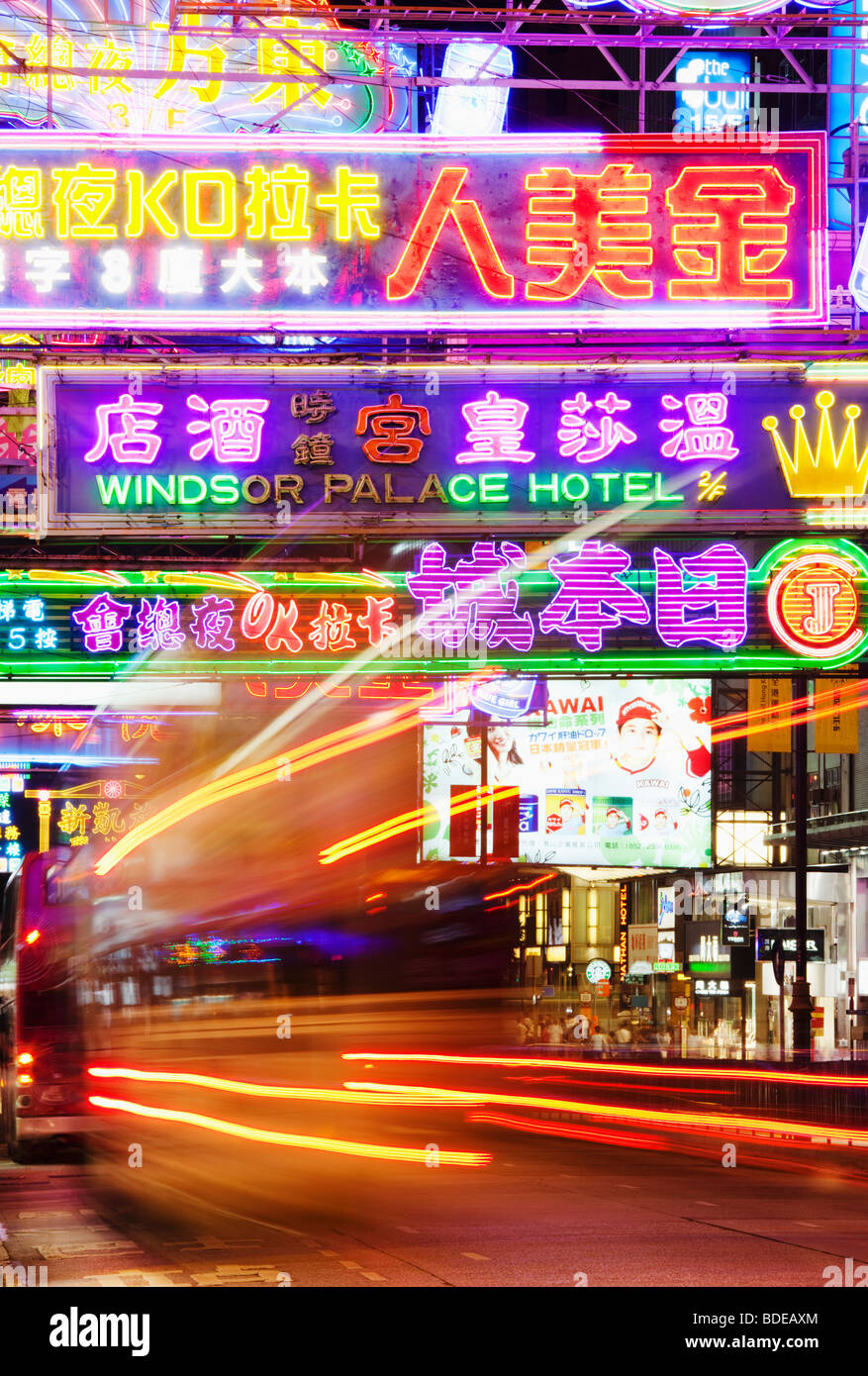 Neon signs and bus light trail in Tsim Sha Tsui, Kowloon, Hong Kong, China. - Stock Image