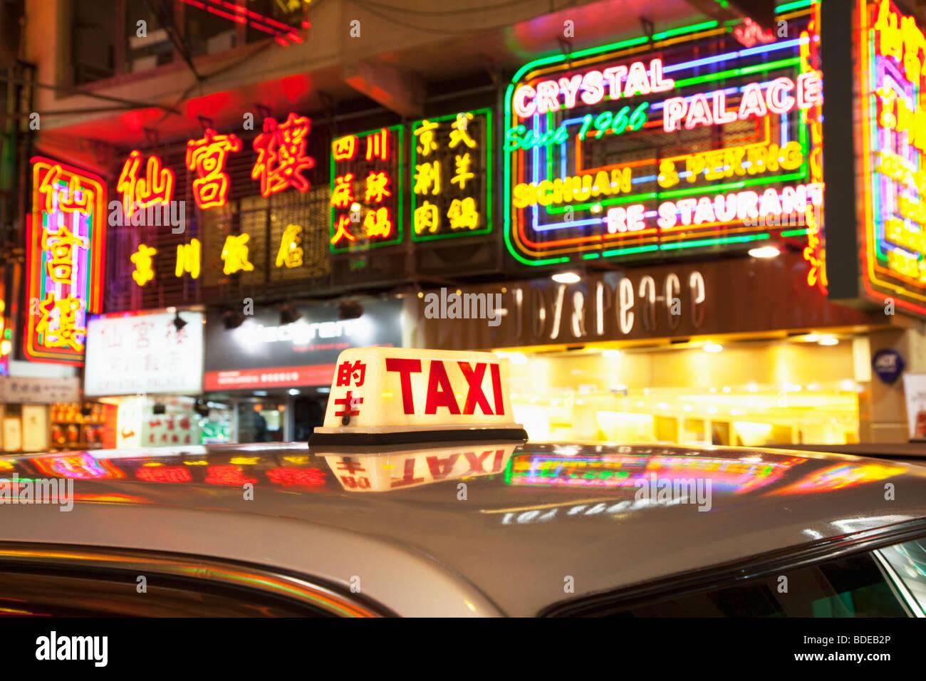 Neon signs and taxi light in Tsim Sha Tsui, Kowloon, Hong Kong, China. - Stock Image