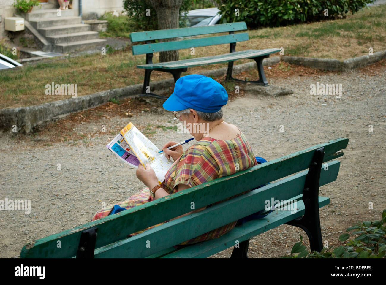 Lady sitting on a bench doing a puzzle in a magazine, Najac, France. - Stock Image