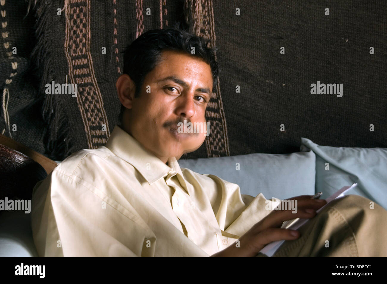 Portrait of a Yemeni man chewing khat or qat - a leafy stimulant and legal drug - in his home in Sanaa, Yemen. - Stock Image