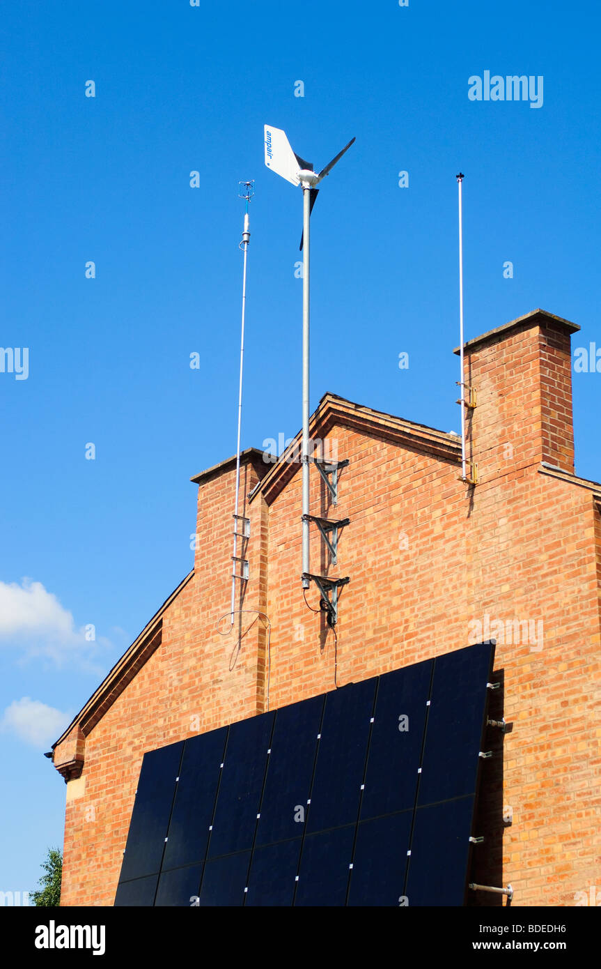 Wind generator and solar panels affixed to the Southerly  wall of a residential house in Leamington Spa, Warwickshire, - Stock Image