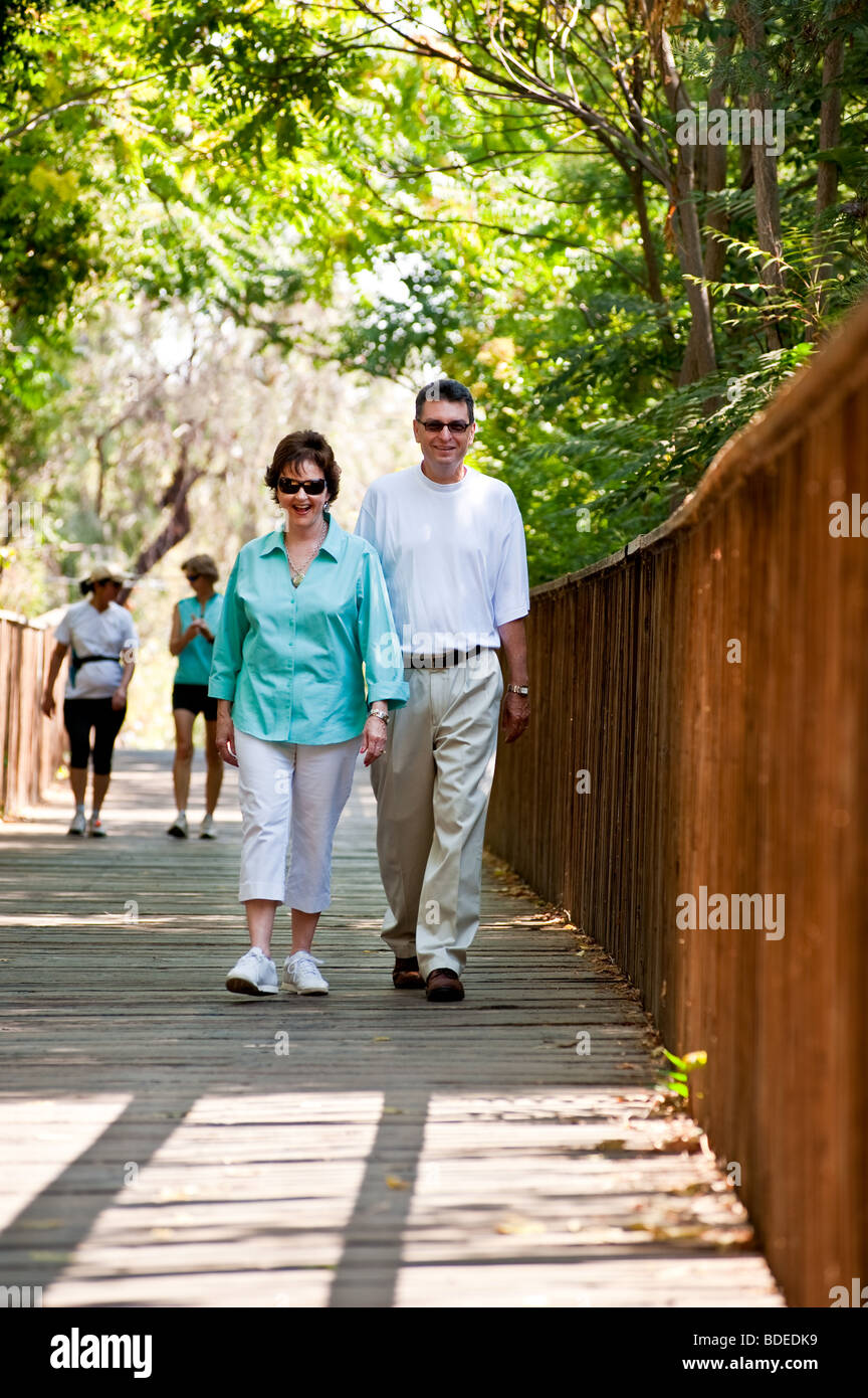Senior couple walk along a wooden nature trail smiling into the camera while being surrounded by trees. - Stock Image