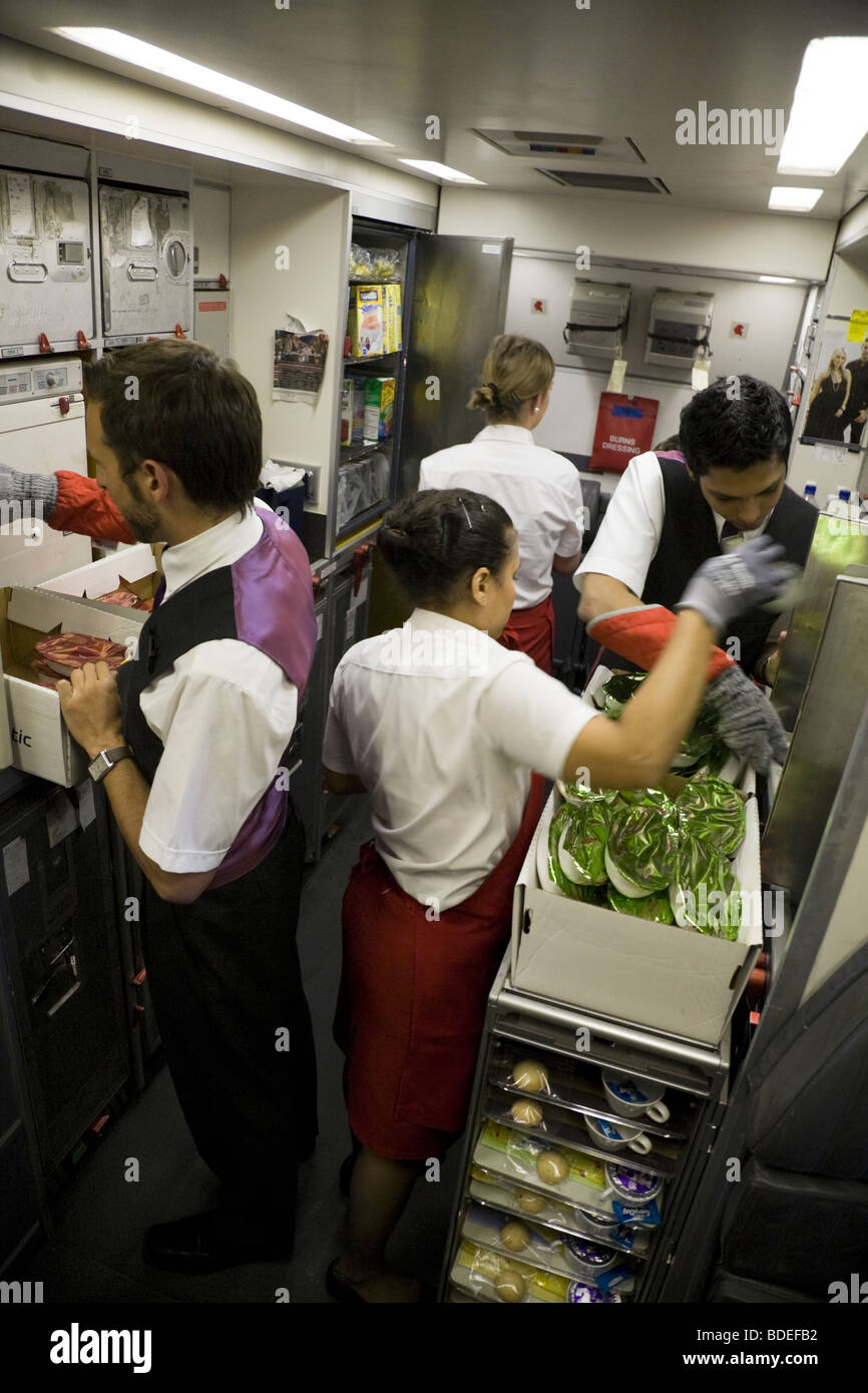 Members of cabin crew prepare to serve meals in the galley of a Virgin Atlantic aircraft during Mumbai to London - Stock Image