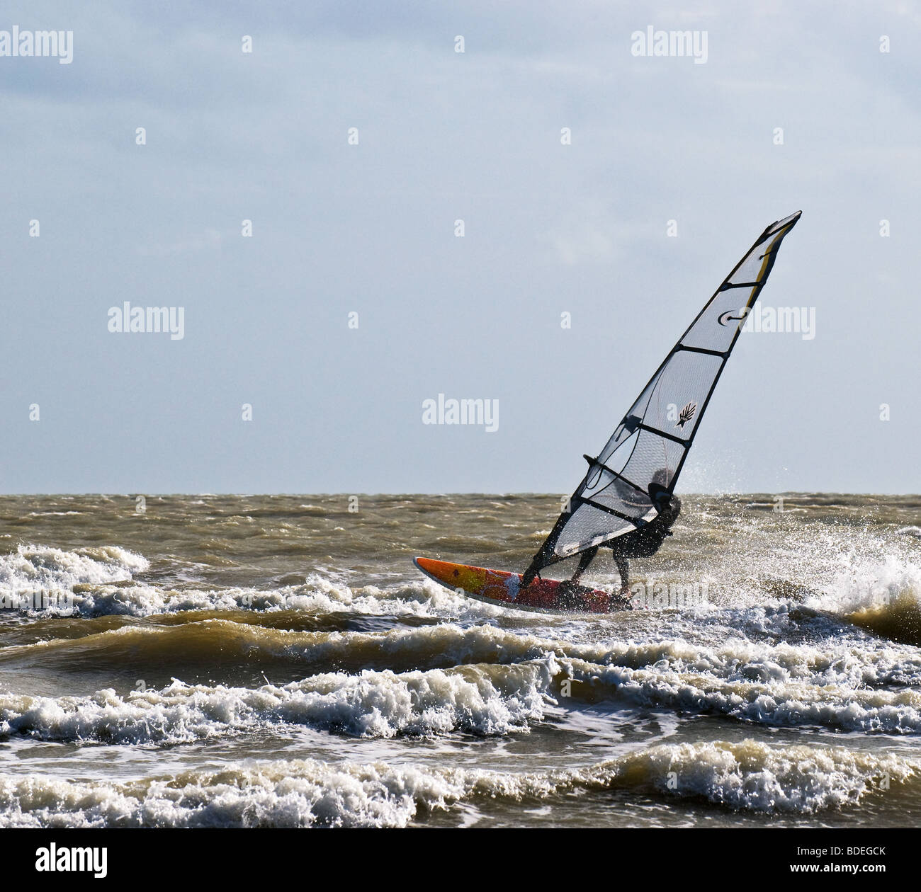A windsurfer in the sea off Camber Sands in Sussex.  Photo by Gordon Scammell - Stock Image