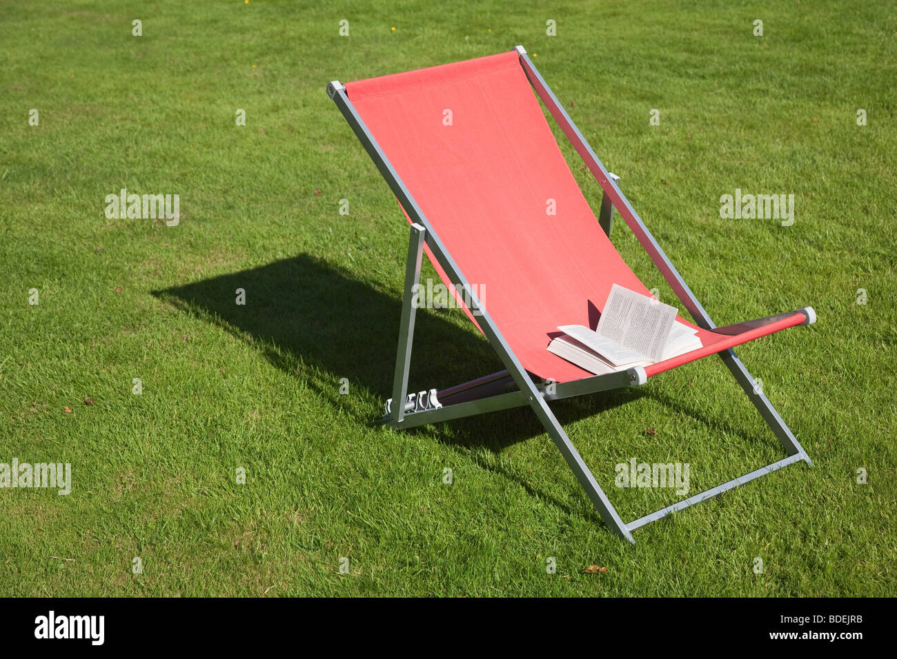 open paperback book on red deckchair - Stock Image