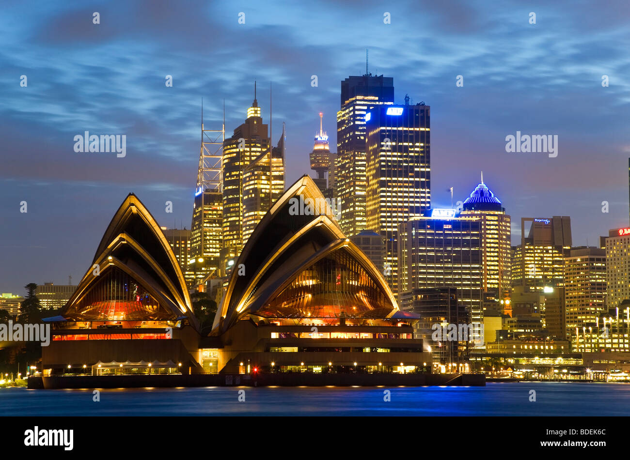 Australia, Sydney, View across Sydney harbour to Sydney Opera House & skyline at dusk - Stock Image