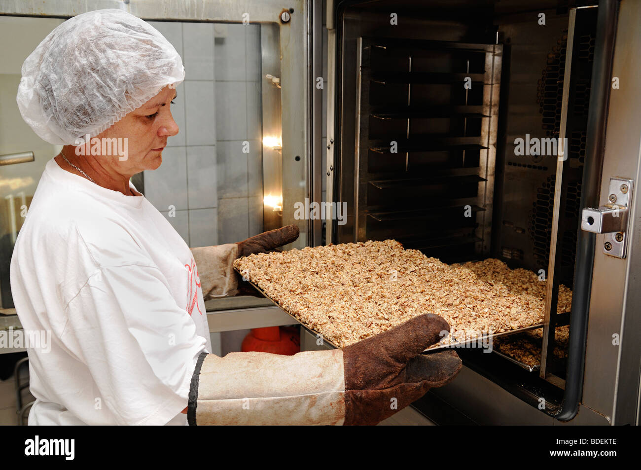 Woman Removing a Tray or Cookies from an Oven in a Commercial Bakery - Stock Image