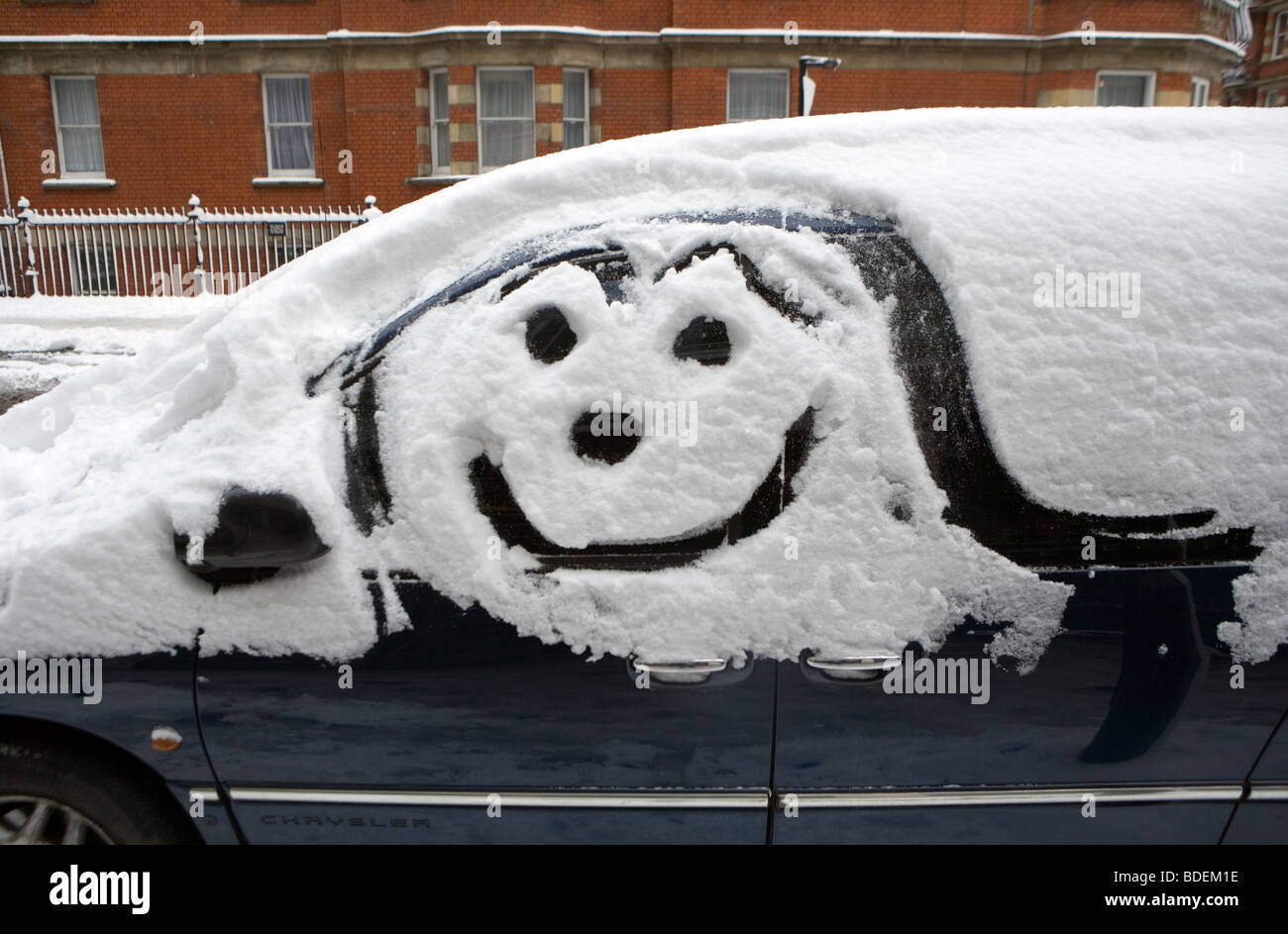 Smiley artwork on parked car after heavy snowfall, London, England, UK, Europe - Stock Image
