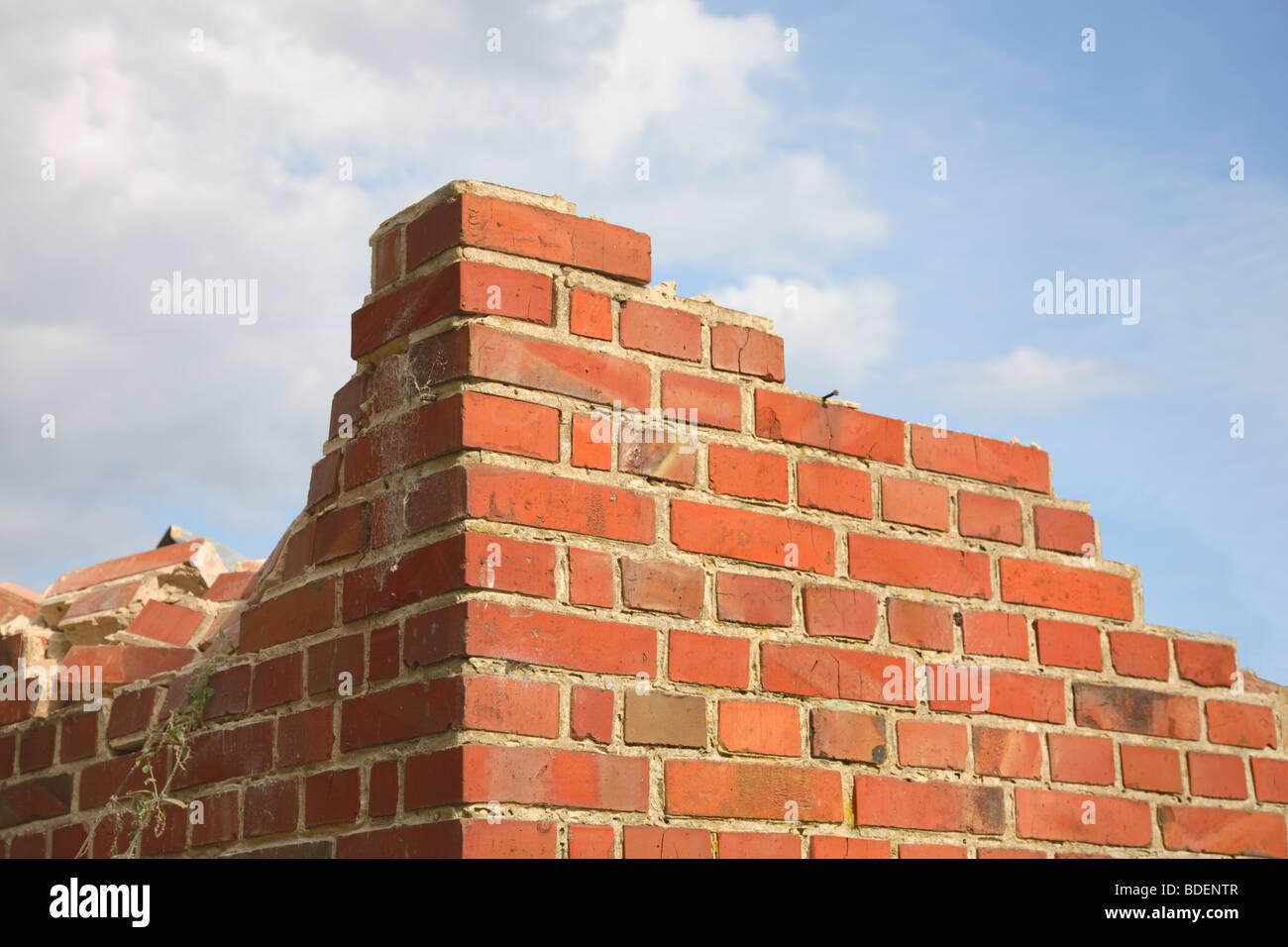 Demolition of a red brick house with one corner of broken bricks left. - Stock Image