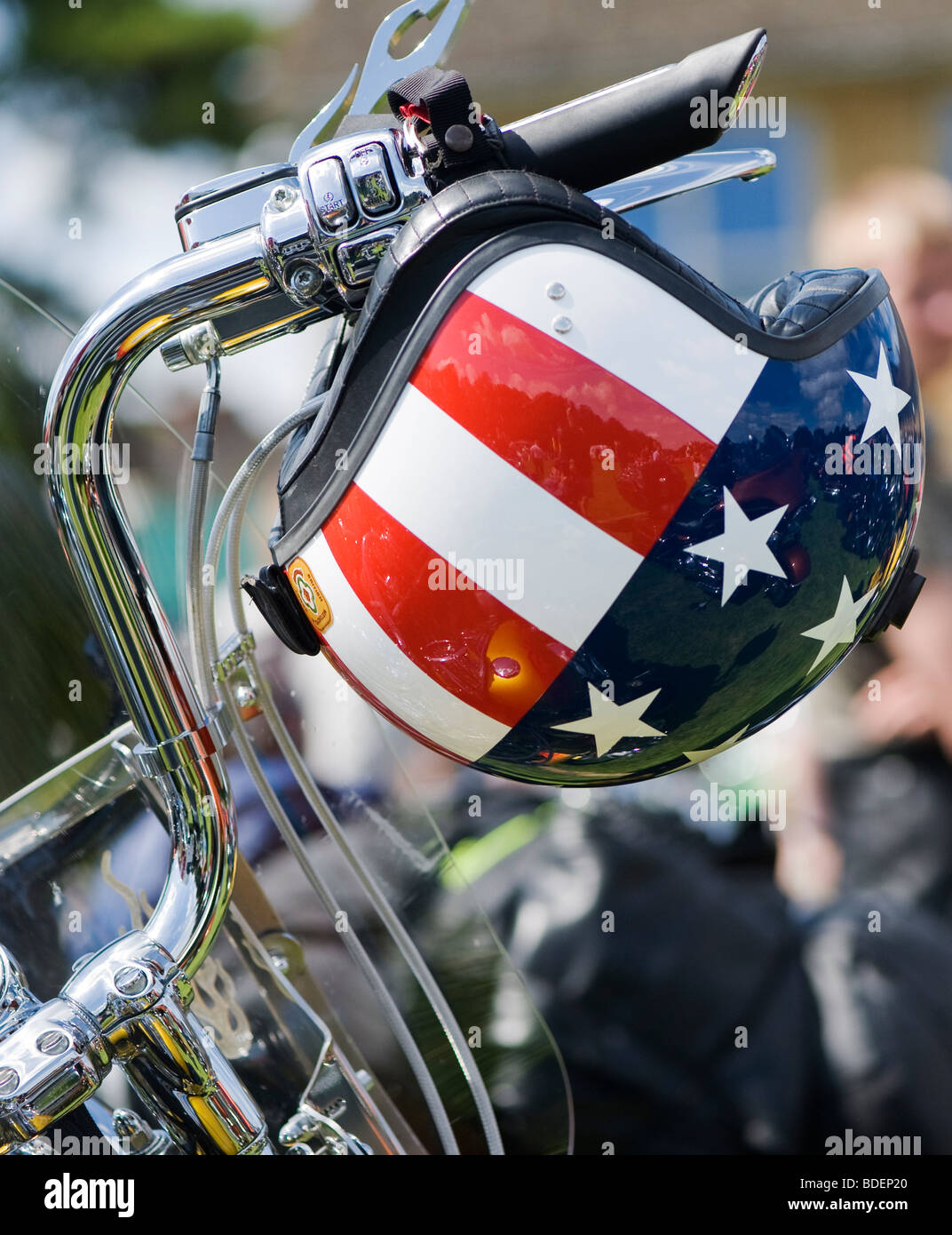 Harley Davidson motorcycle with a custom American 'stars and stripes flag' helmet on the handlebars - Stock Image