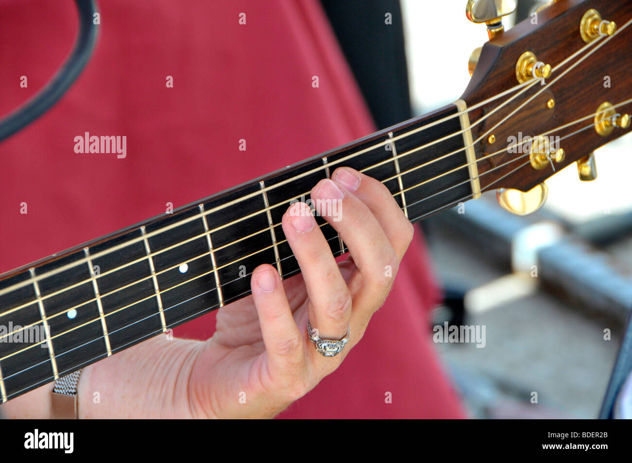Hand playing a string guitar - Stock Image