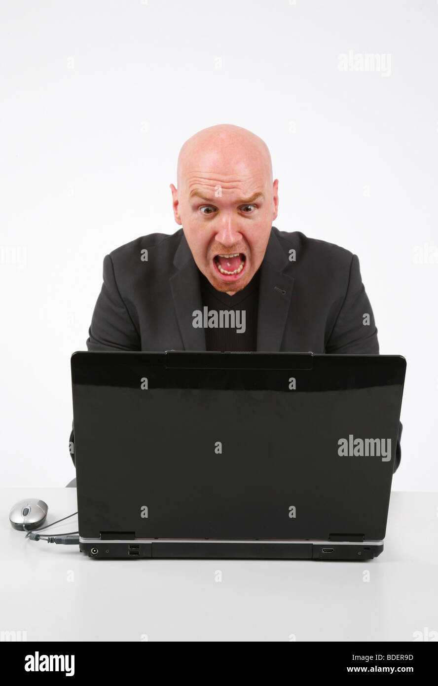 bald headed man looking appalled at his laptop - Stock Image