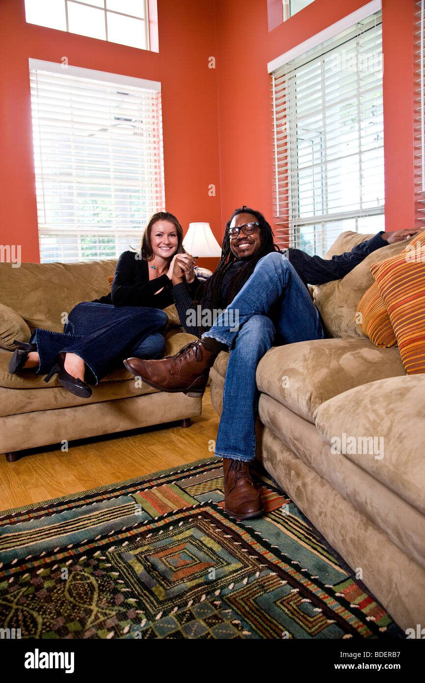 Interracial couple sitting on couch in living room - Stock Image