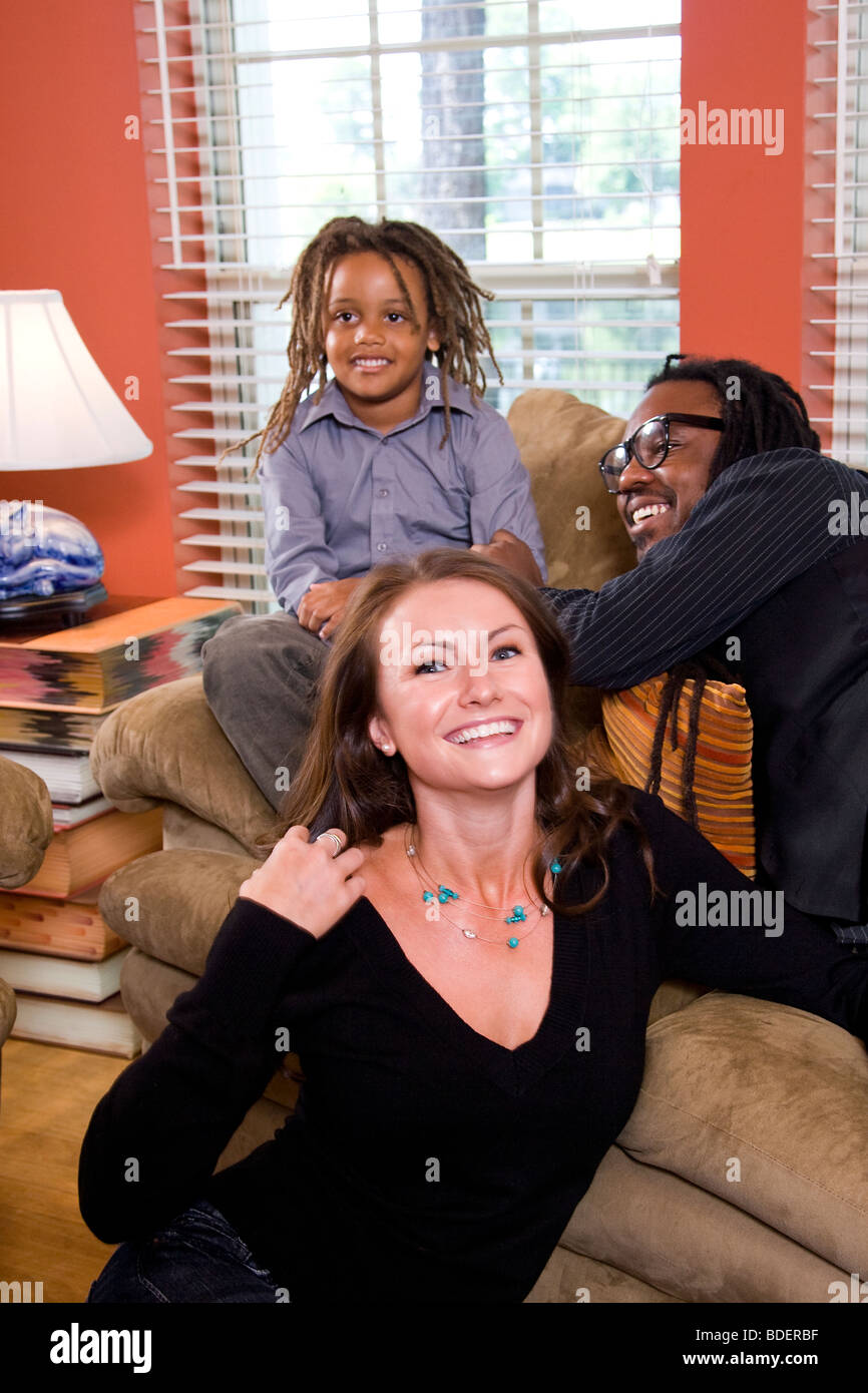 Mixed race family sitting on couch in living room - Stock Image