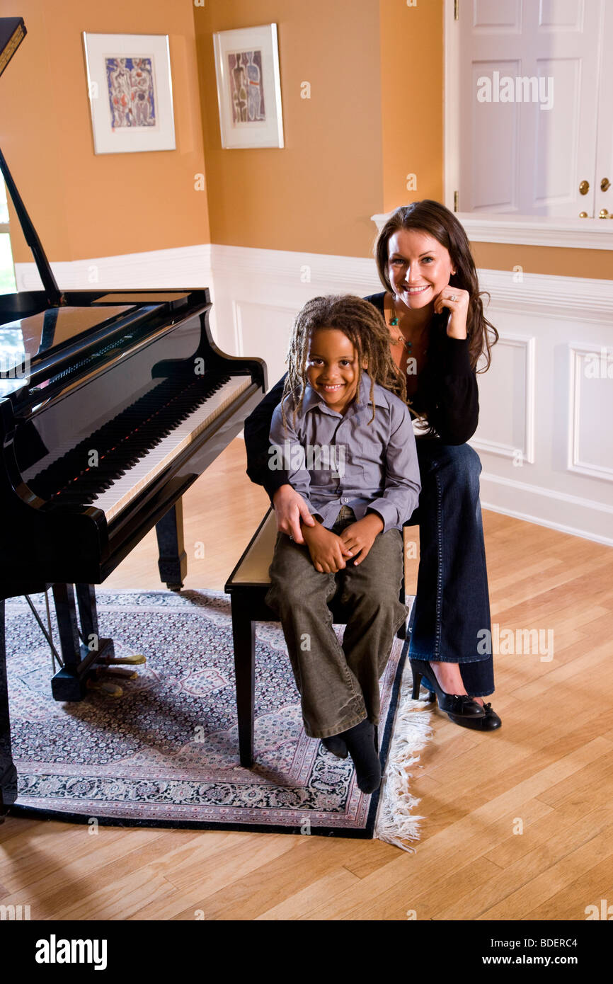 Portrait of mixed race mother and son sitting at piano - Stock Image