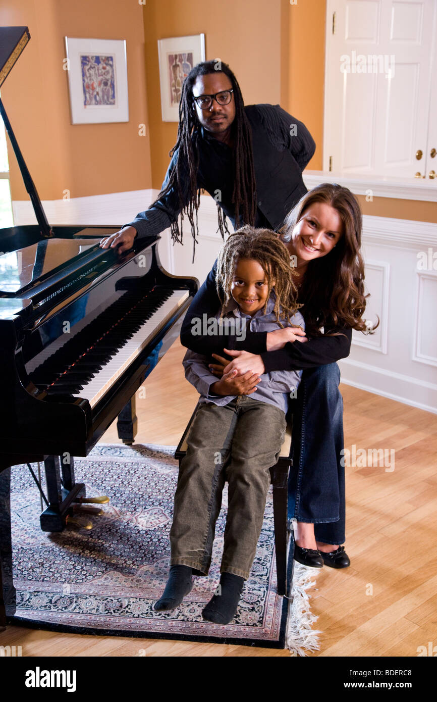 Portrait of mixed race family sitting around piano - Stock Image