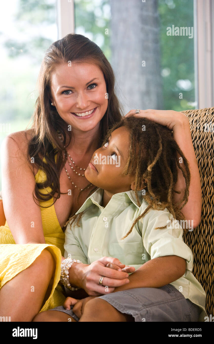 Mother with mixed-race son sitting on couch in sunroom - Stock Image