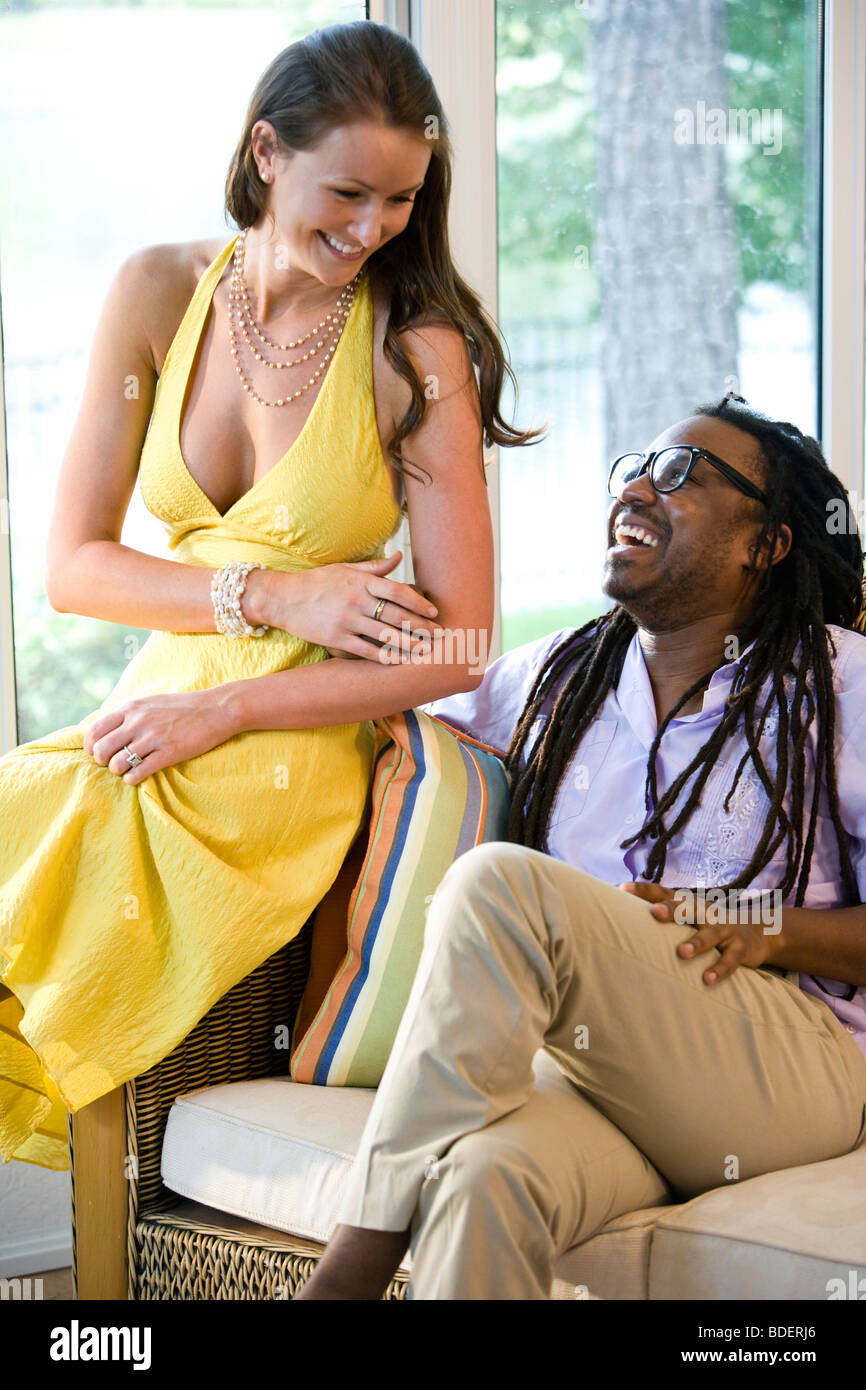 Interracial couple relaxing together in sunroom - Stock Image
