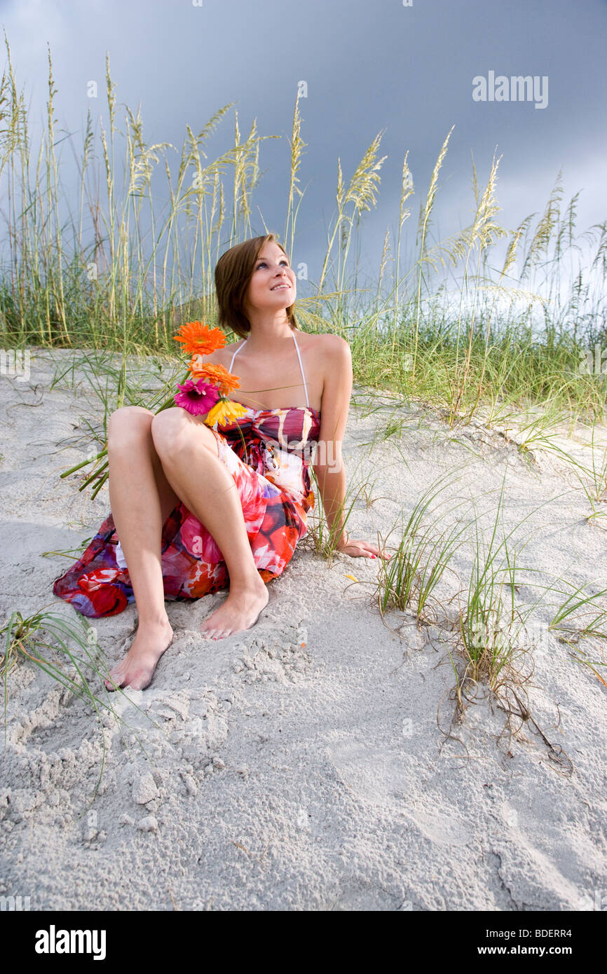 Young woman in colorful sundress sitting on beach holding flowers - Stock Image