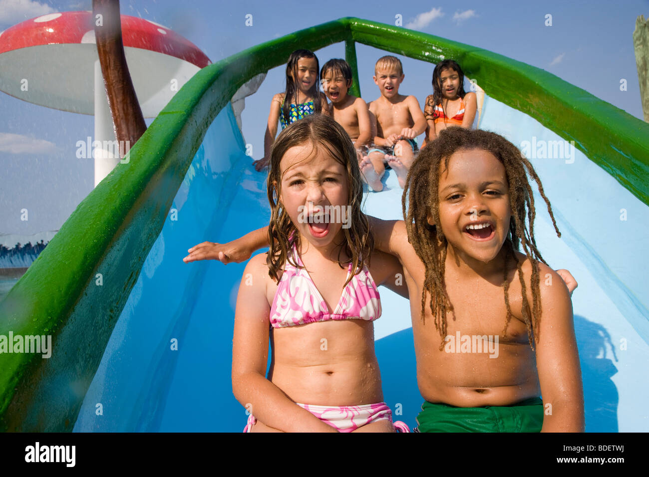 Multi-ethnic children on waterslide at water park Stock Photo