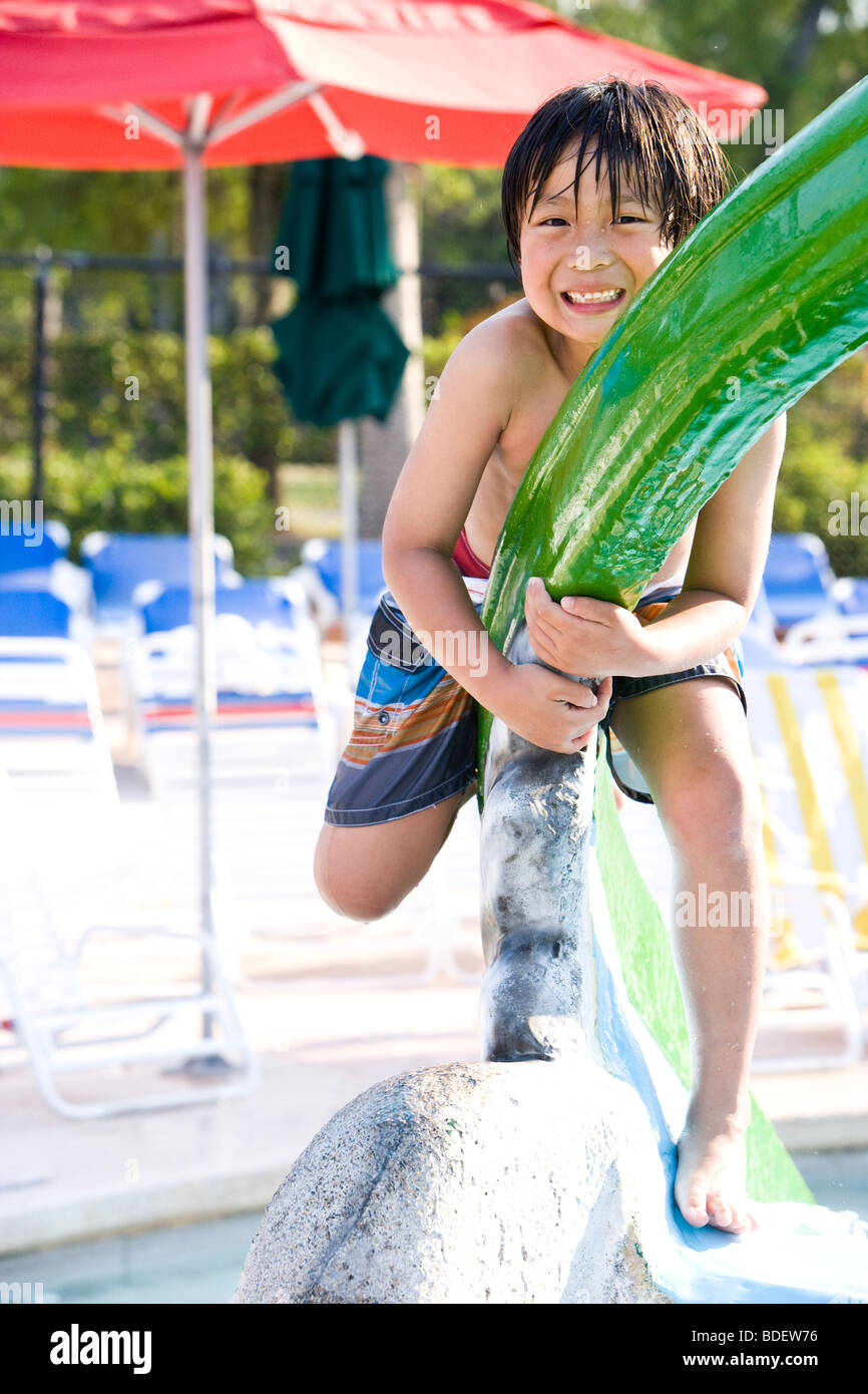 Young Asian boy playing at water park in summer