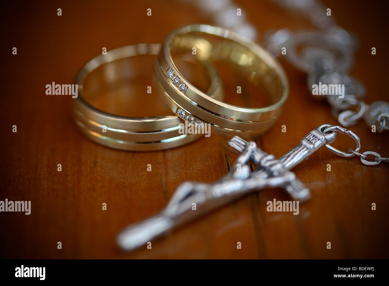 Pair of wedding rings with Christian crucifix on chain Stock Photo
