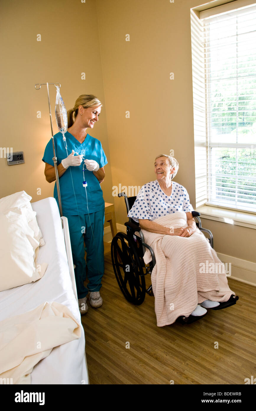 Nurse and senior woman in wheelchair in hospital room - Stock Image