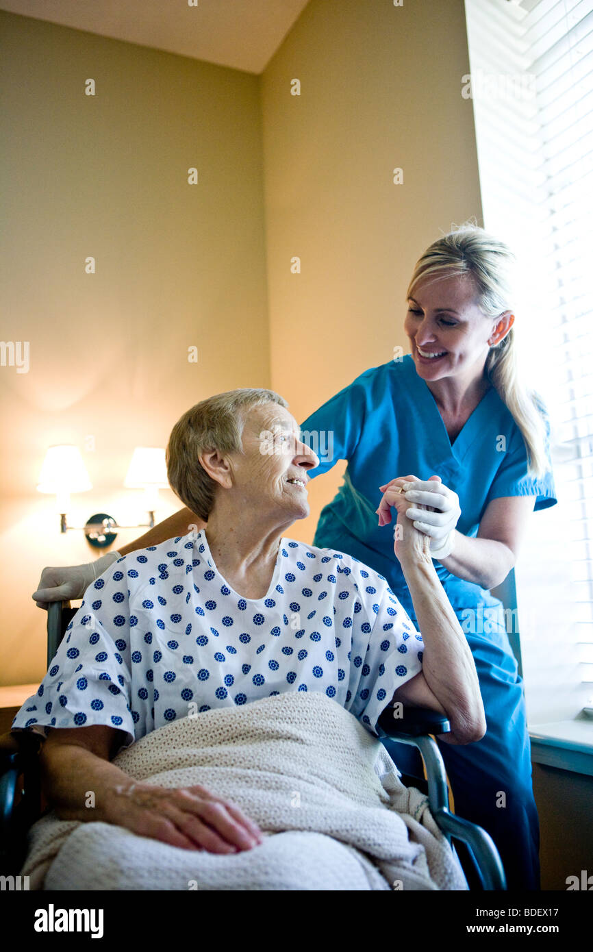 Nurse and elderly woman in wheelchair in hospital room - Stock Image