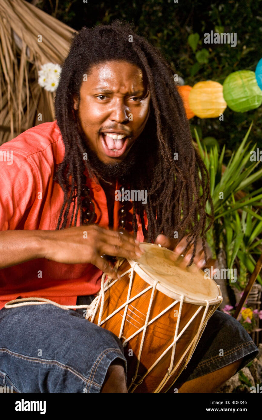 Young Jamaican man with dreadlocks playing bongo on tropical island - Stock Image