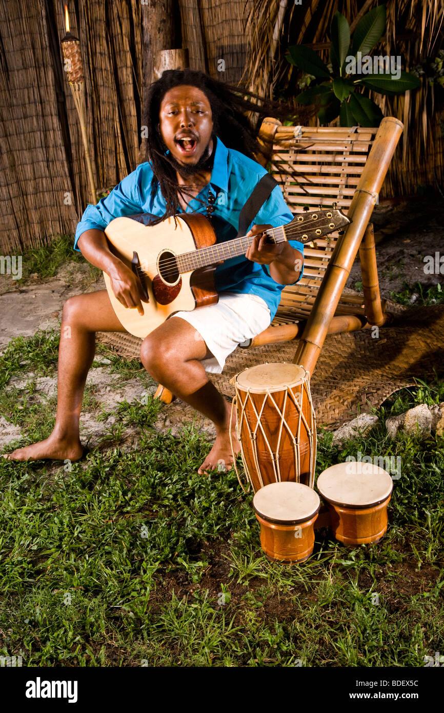 Young Jamaican man with dreadlocks playing guitar and bongos on tropical island - Stock Image