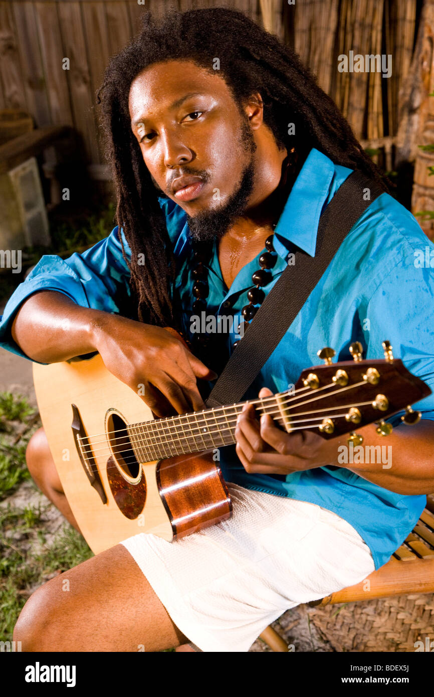 Portrait of young Jamaican man with dreadlocks holding guitar on tropical island Stock Photo